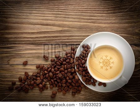 White coffee cup and coffee beans on old dark wooden background.