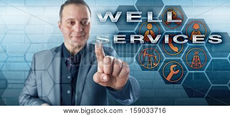 Happy male operations supervisor with toothless smile and positive demeanor is touching WELL SERVICES on an interactive control screen. Industrial concept for oil wells and petroleum production.