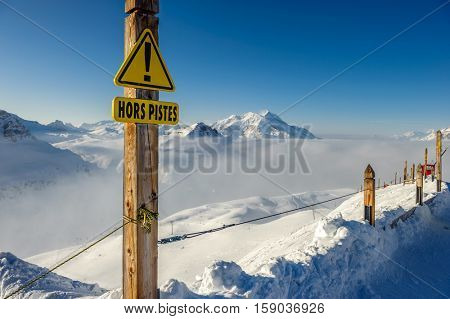 Off-piste sign in french language at Alpine winter mountain landscape with low clouds. French Alps covered with snow in sunny day. Val-d'Isere, France