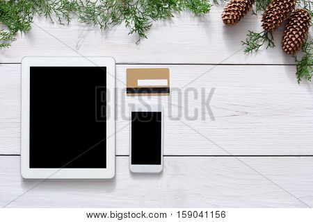 Christmas online shopping background. Cell phone and tablet screen with copy space top view on white wood, credit card and. Mobile applications and internet commerce on winter holidays concept