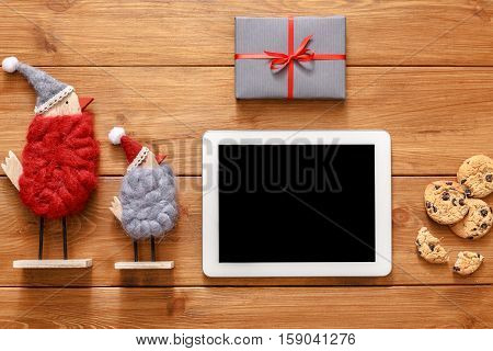 Christmas online shopping background. Tablet screen with copy space top view on wood, xmas toys ans presents. Electronic devices, internet commerce on winter holidays concept