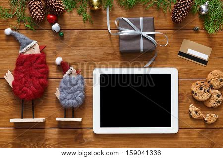 Christmas online shopping background. Tablet screen with copy space top view on wood, credit card, xmas toys ans presents. Electronic devices, internet commerce on winter holidays concept