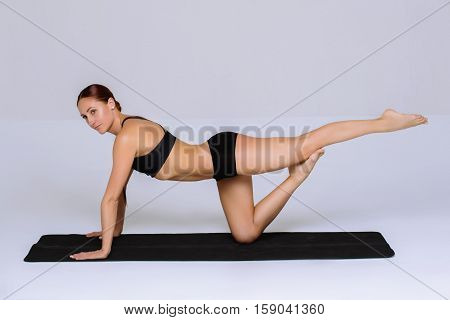 Fitness woman in sports skinny clothing looking away. Slim female model with flexible body. Horizontal studio shot with copy space on gray background.