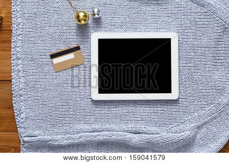 Christmas online shopping background. Tablet screen with copy space top view on warm knitted sweater cloth and credit card. Electronic devices, internet commerce on winter holidays concept