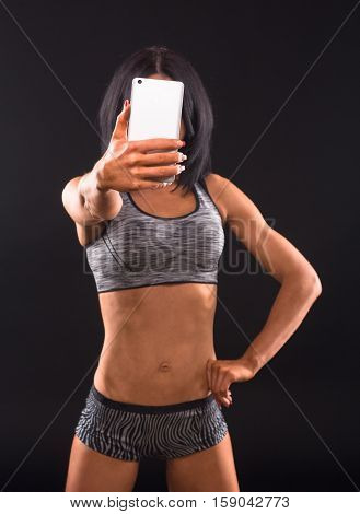 Sports, gym concepts. Brunette fitness woman making self photos on mobile or smart phone and demonstrating her fitness body isolated on black in studio.