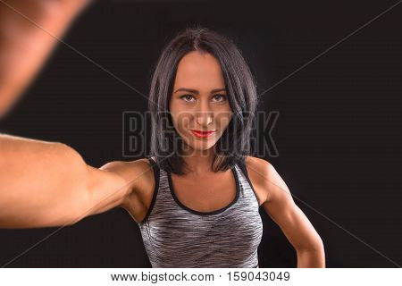 Gym concept. Muscular lady making self photos while posing for photographer. Brunette sports lady looking at camera in studio.