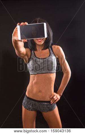 Fitness and bodybuilding concepts. Picture of beautiful brunette fitness lady making self photos on mobile phone while demonstrating her perfect abs for photographer.