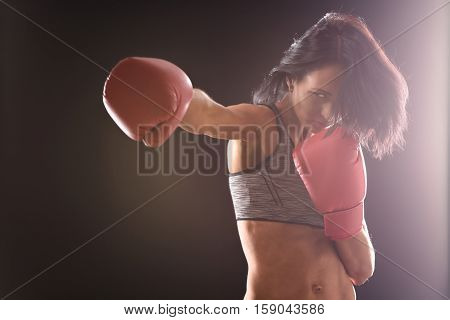 Young beautiful woman during fitness and boxing. Boxer woman making several direct hits over black background in studio.