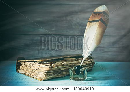 Feather pen in inkwell near old book on wooden background