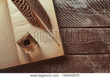 Feather pen with inkwell and open notebook on wooden table closeup