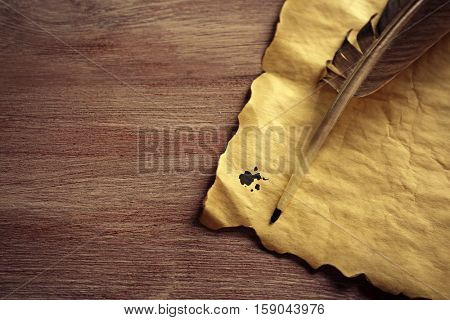 Feather pen and blank paper on wooden background