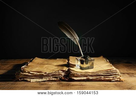 Feather pen with inkwell and stack of papers on dark background