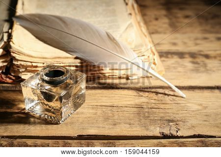 Feather pen with inkwell and stack of papers on wooden table closeup