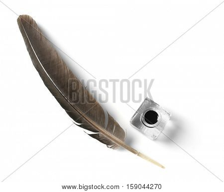 Feather pen and inkwell isolated on white