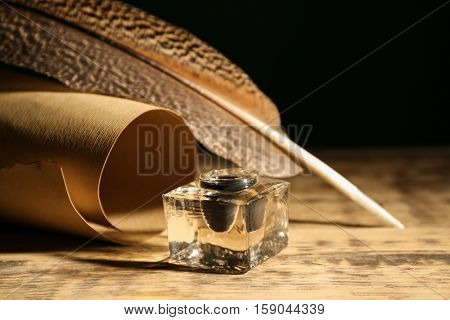Feather pen with inkwell and scroll on wooden table closeup