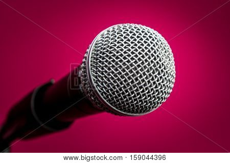 Microphone with metal body in holder isolated on crimson background close-up
