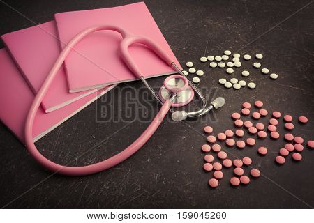 Notebooks, stethoscope and pills on dark background