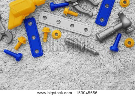 Set of plastic toy tools on a carpet