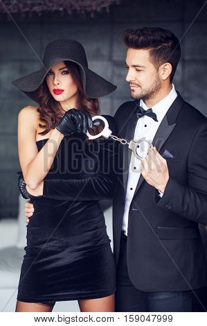 Sexy dominatrix woman holding on handcuffs young macho lover in tuxedo bdsm