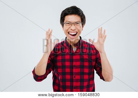 Image of screaming young man dressed in casual shirt in a cage and wearing eyeglasses gesturing with hands. Isolated over white background. Eyes closed.