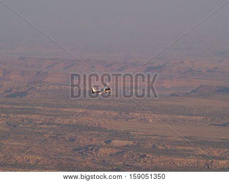 Single engine plane flying over wide open desert
