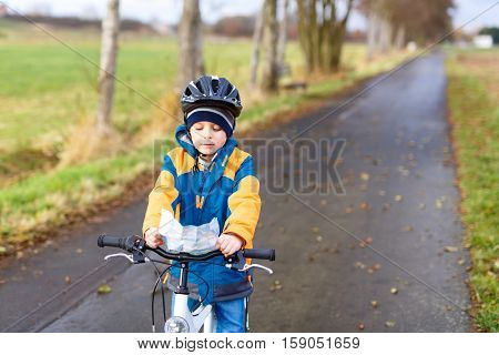 Active preschool kid boy in helmet biking on bicycle and reading map. Happy child in colorful clothes. Safety and protection for children. Active leisure in autumn, winter, spring for kids.