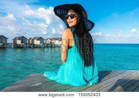 Portrait of happy young woman at beautiful water villa at Maldives island. Travel and Vacation. Outdoor shot