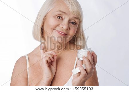 Anti age cosmetics. Delighted nice good looking woman applying anti age cream of her neck and smiling while using anti age cosmetics