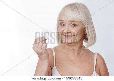 Daily skin care routine. Positive grey haired elderly woman holding a cotton pad and looking at you while standing against the white background