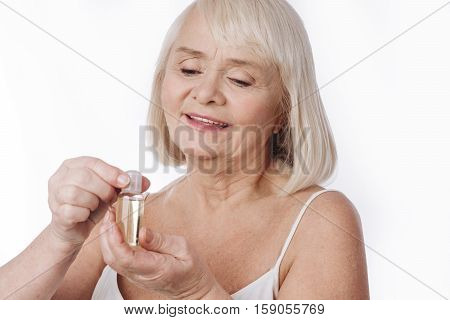Skin care products. Serious nice aged woman holding a bottle with skin lotion and opening it while intending to use it