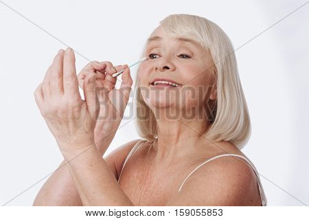 Daily skin care. Pleasant elated grey haired woman holding a cotton bud and looking at her hand while putting on cream around her eyes