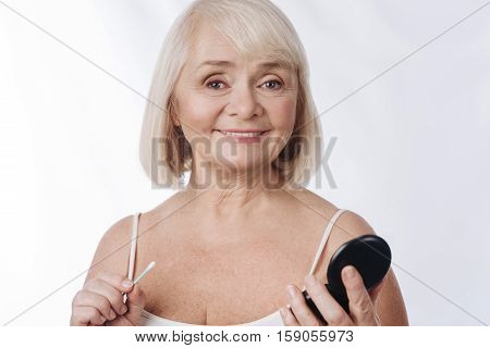 Against white background. Pleasant nice grey haired woman holding a small mirror and a cotton swab and smiling while looking at you