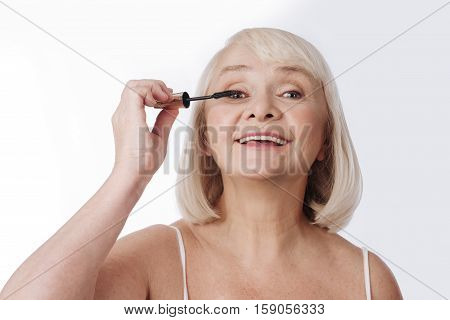 Expressive look. Delighted elderly optimistic woman holding a mascara brush and using it while making her eyelashes look bigger