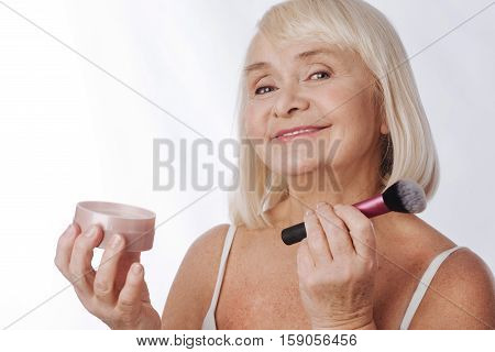 Make up accessories. Positive optimistic retired woman using a makeup brush and holding face powder while using decorative cosmetics