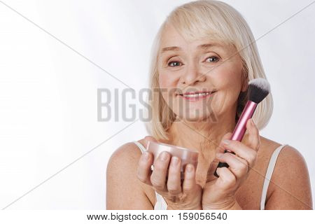 Conceal skin imperfections. Cheerful good looking retired woman holding a cosmetic brush and using face powder while concealing skin imperfections