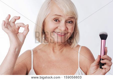 Everything is all right. Nice optimistic aged woman holding a makeup brush and showing OK sign while being in a wonderful mood