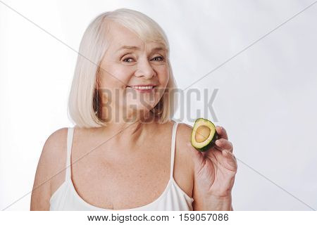 Exotic fruits. Cheerful nice aged woman holding an avocado half and smiling while looking at you