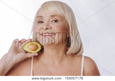 Doze of vitamins. Joyful positive aged woman standing against the white background and smiling while holding half of the avocado