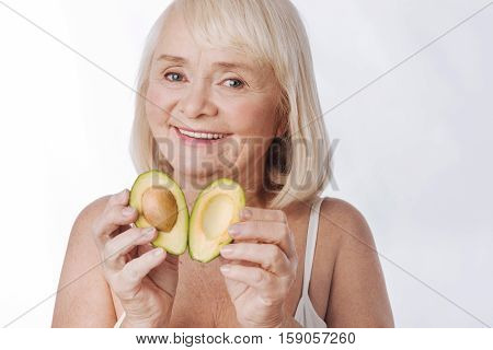 Two parts of one. Nice delighted retired woman holding two avocado halves and putting them together while smiling