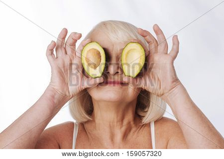 Avocado halves. Nice good looking grey haired woman holding avocado halves near her eyes and smiling while standing against the white background