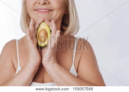 Delicious fruit. Close up of an avocado half with a pit being in hands of a good looking nice elderly woman