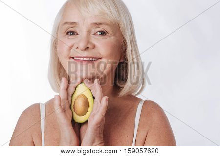 Natural cosmetics. Cheerful smiling senior woman holding an avocado fruit and looking at you while standing against the white background