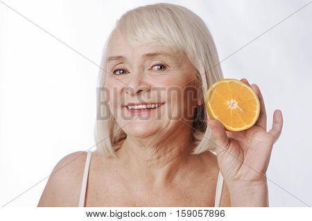 Orange fruit. Cheerful positive senior woman holding a citrus fruit and smiling while looking at you