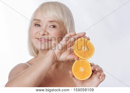Citrus tower. Delighted charming retired woman holding orange halves and making a small tower from them while looking at you