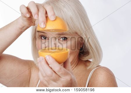 Between orange halves. Optimistic senior grey haired woman holding two parts of an orange and looking it you while being in a good mood