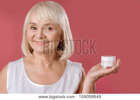 Professional cosmetics. Delighted content elderly woman holding a bottle of skin lifting cream and smiling while standing against pink background