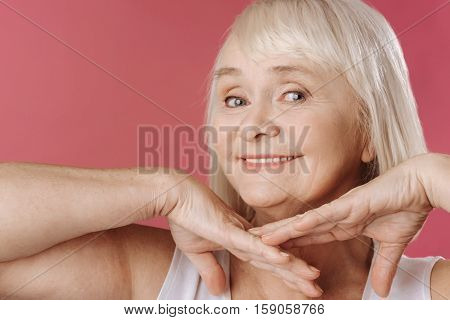 Nice face. Happy charming retired woman holding her hands under the chin and looking at you while feeling great