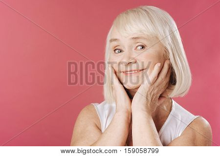 I am beautiful. Pleasant good looking grey haired woman holding her hands up and touching her cheeks while standing against pink background