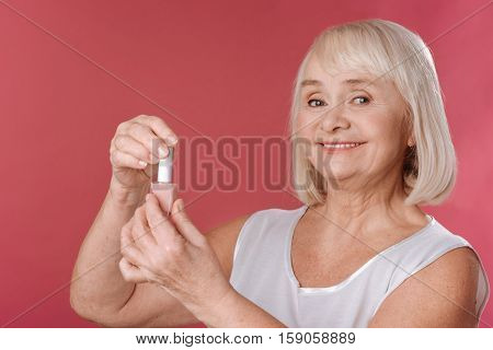 Beautiful nails. Pleasant good looking retired woman holding a bottle of nail varnish and opening it while doing her manicure