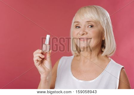 Nude colors. Good looking charming aged woman holding nail varnish and smiling while standing against pink background